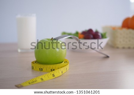 Tape measure around the green apple. Next there are milk and vegetable salad on the wooden table. Eating for good health and weight loss. Diet concept #1351061201