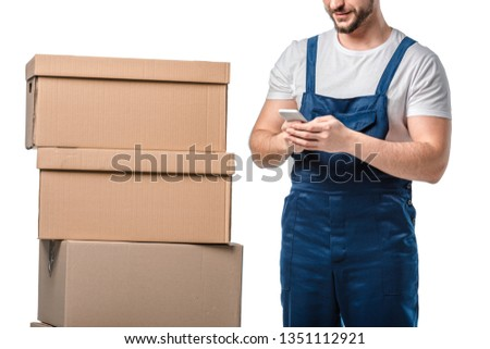 cropped view of mover with cardboard boxes using smartphone isolated on white #1351112921