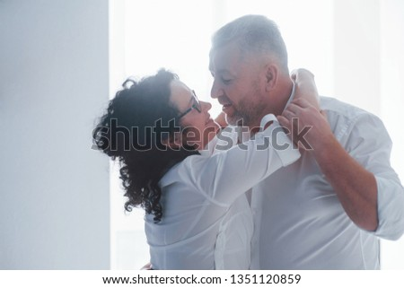 Senior man and his wife in white shirt have romantic dinner on the kitchen. #1351120859