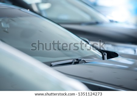 Close-up pictures of windshields and wipers of new cars showing on showrooms, new cars for sale