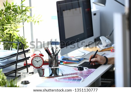 Designer male arm hold graphic pad pen working on project at home computer closeup background