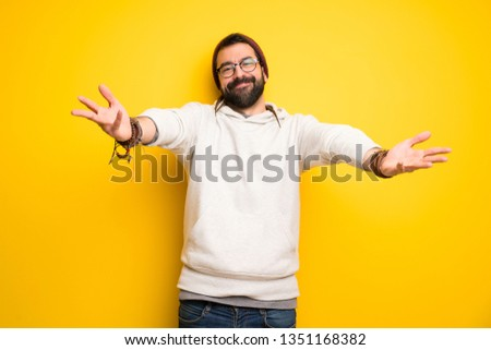 Hippie man with dreadlocks presenting and inviting to come with hand #1351168382