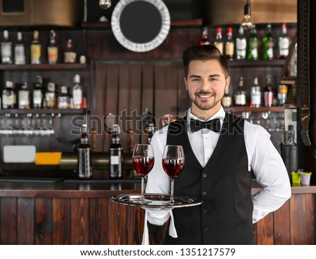 Young male waiter with glasses of wine in restaurant #1351217579