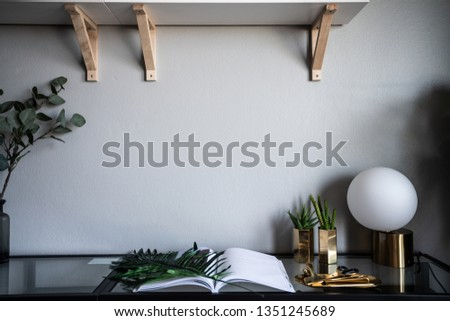Stylish Working corner with artificial cactus in  gold mirror vase and open book on clear glass working table with empty gray  painted wall in the background / copy space / work from home