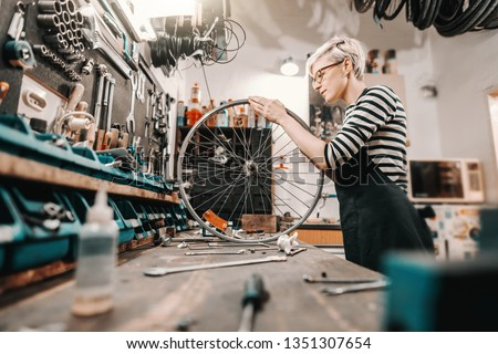 Cute Caucasian female worker holding and repairing bicycle wheel while standing in bicycle workshop. #1351307654