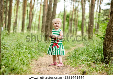 Russia, Stavropol, 25/08/2018. citi park. baby girl running on green grass,baby girl blonde in a beautiful dress running on the green grass. the concept of walks in the fresh air #1351441664