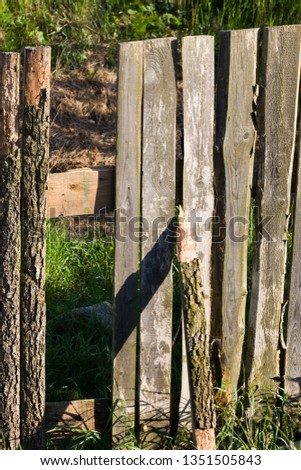 The old wooden fence is made of scraps of trees and old boards, close-up of the structure protecting the necessary territory #1351505843