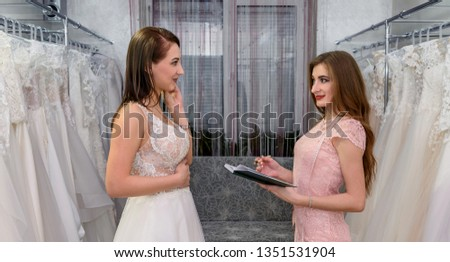 Designer with notepad and woman customer in wedding store #1351531904