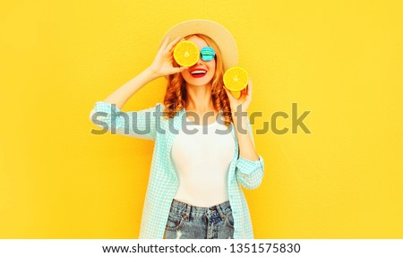Summer portrait happy smiling woman holding in her hands slices of orange hiding her eyes in straw hat on colorful yellow background #1351575830