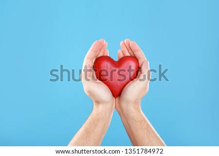 Man holding decorative heart in hands on color background, closeup #1351784972