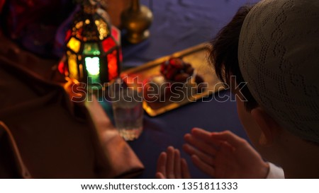 Man praying. Breaking the fast. Fasting the month of Ramadan. Iftar: the Daily Break Fast During Ramadan #1351811333