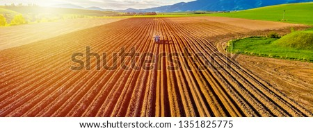 Farmer in tractor preparing land with seedbed cultivator in farmlands. Tractor plows a field. Agricultural work in processing, cultivation of land. Furrows row patter. aerial photo #1351825775