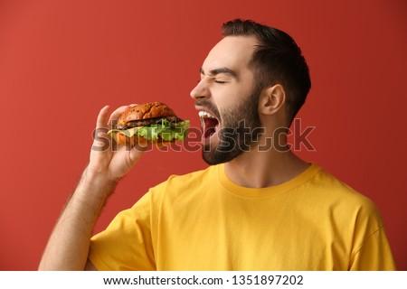 Man eating tasty burger on color background #1351897202