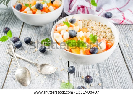Healthy breakfast oatmeal with tropical fruits and berries, on white wooden background copy space #1351908407