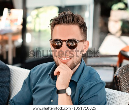 Portrait picture of young man in blue shirt looking at the camera. Handsome businessman wearing sunglasses. Good looking man smiling. In a cafe outdoors. #1351910825