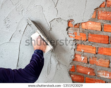 Construction under building with mason plastering concrete to brick wall #1351923029
