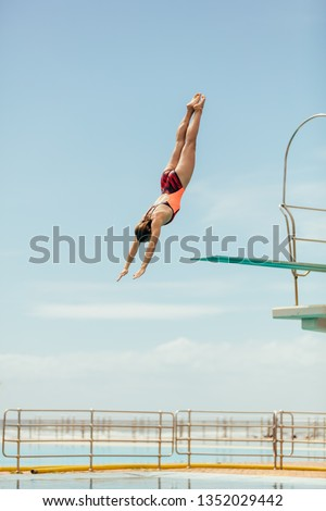 Woman diving into the pool from spring board. Female diver diving upside down into the swimming pool. Royalty-Free Stock Photo #1352029442