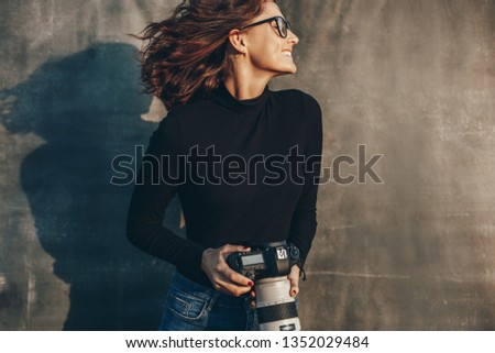 Beautiful female photographer with a professional camera against muslin backdrop. Cheerful young woman photographer with digital camera.