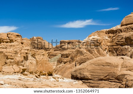 high rocky mountains in the desert against the blue sky and white clouds in Egypt Dahab #1352064971