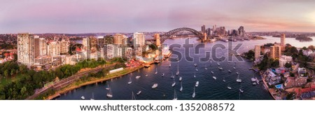 Wide panoramic cityscape of Sydney city CBD landmarks on waterfront of Sydney harbour over Lavender bay from North Shore at sunset. #1352088572