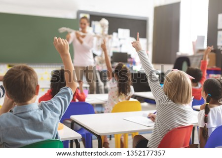Rear view of kids raising hands while teacher explaining the functioning of human skeleton in classroom at school Royalty-Free Stock Photo #1352177357