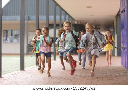 Front view of happy diverse school kids running in corridor at school #1352249762