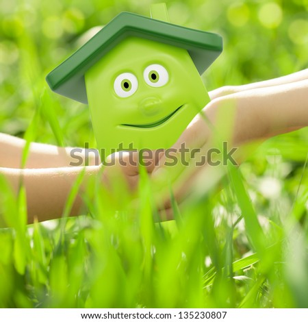 Eco cartoon house in hands against spring green background. Family home concept