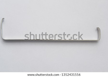 surgical retractor on white surface #1352431556