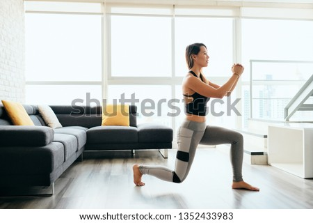 Fit young Pacific Islander woman training at home. Beautiful female athlete working out for wellbeing in domestic gym, training legs muscles doing lunges exercise #1352433983