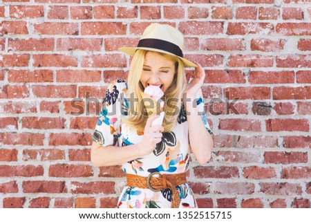 Girl with fedora hat bites into an ice cream cone in the summer and feels pain due to tooth sensitivity #1352515715