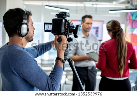 Happy businessman during corporate interview with female journalist. Manager answering question in office. Young woman at work as reporter with business man and cameraman shooting video for broadcast Royalty-Free Stock Photo #1352539976