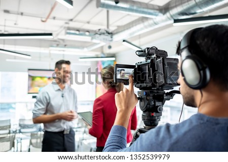 Happy businessman during corporate interview with female journalist. Manager answering question in office. Young woman at work as reporter with business man and cameraman shooting video for broadcast #1352539979