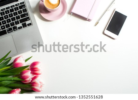 Home office desk in pink colors with laptop, cup of coffee, rose notebook, phone, pink tulips on a white background. Flat lay Business womans workplace and objects.  Top view. Copy space for text