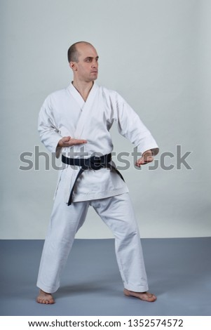 On a gray covering male athlete trains formal karate exercises #1352574572