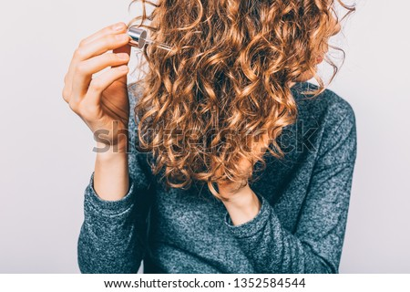 Young woman holding pipette with nutritional oil applying on her thick curly hair. Female's hands using cosmetic serum to prevent split ends. #1352584544