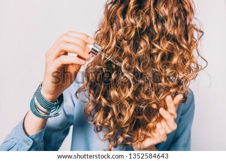 Close-up young woman in blue shirt holding her curly brown hair applying moisturizing oil with pipette. #1352584643