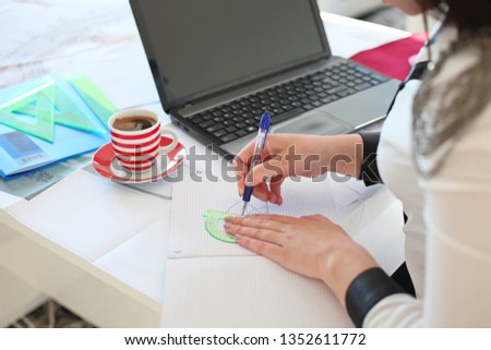 Young businesswoman sitting at table with modern laptop at home and writing and processing photos.-Image #1352611772
