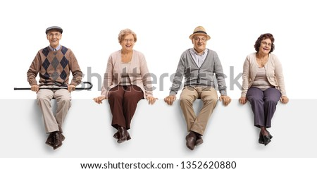 Full length portrait of two senior men and two senior women sitting on a white panel and posing isolated on white background  #1352620880