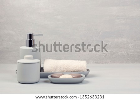 Light gray ceramic acessories for bath - bowl, soap dispenser and other accessories for personal hygiene. Decor for bathroom interior #1352633231