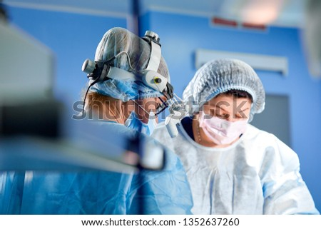 Surgeon and his assistant performing cosmetic surgery in hospital operating room. Surgeon in mask wearing loupes during medical procadure. #1352637260