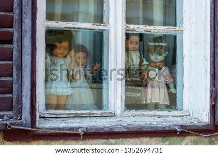 Four creepy dolls dressed in white and with traditional Romanian clothes, displayed in a window, while looking at the people passing by. Close up of puppets - horror concept. #1352694731