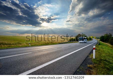 White bus traveling on the asphalt road in rural landscape at sunset with dramatic clouds                                #1352760209
