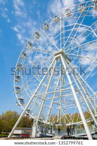 Ferris wheel an amusement-park or fairground ride consisting of a giant vertical revolving wheel with passenger cars suspended on its outer edge. #1352799761