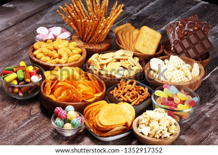 Salty snacks. Pretzels, chips, crackers in wooden bowls. Unhealthy products. food bad for figure, skin, heart and teeth. Assortment of fast carbohydrates food.  Royalty-Free Stock Photo #1352917352