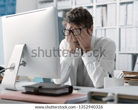 Tired stressed businessman working at office desk, he is rubbing his eyes and feeling exhausted #1352940326