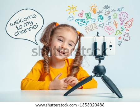 beautiful cute little blogger girl recording a video on smartphone for her followers. Little blogger girl saying welcome to my channel in cartoon balloon. Media icons flying over the smartphone