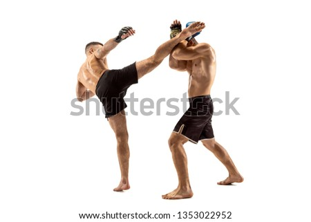 MMA. Two professional fightesr punching or boxing isolated on white studio background. Couple of fit muscular caucasian athletes or boxers fighting. Sport, competition, excitement and human emotions Royalty-Free Stock Photo #1353022952