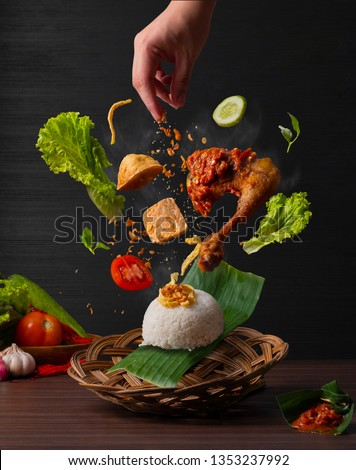 Flying traditional fried chicken with sambal on top, fried tofu, fried soybean cake, fresh lettuce, fresh tomatoes, eggs, fried onion and steamed coconut milk rice or in other word, nasi uduk #1353237992