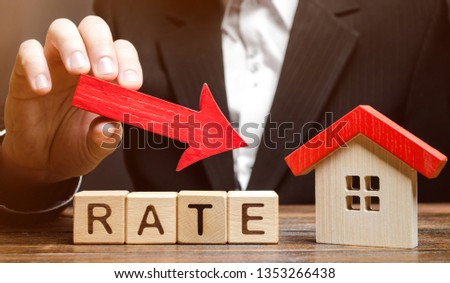 Businessman holding the down arrow on wooden blocks with the word Rate and house. Low interest in mortgages. Reducing interest payments for mortgage. The fall in housing rates on credit. #1353266438