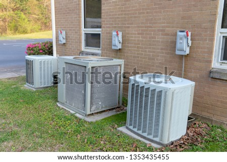 3 Air Conditioner Compressors outside commercial building with cutoff switches. #1353435455